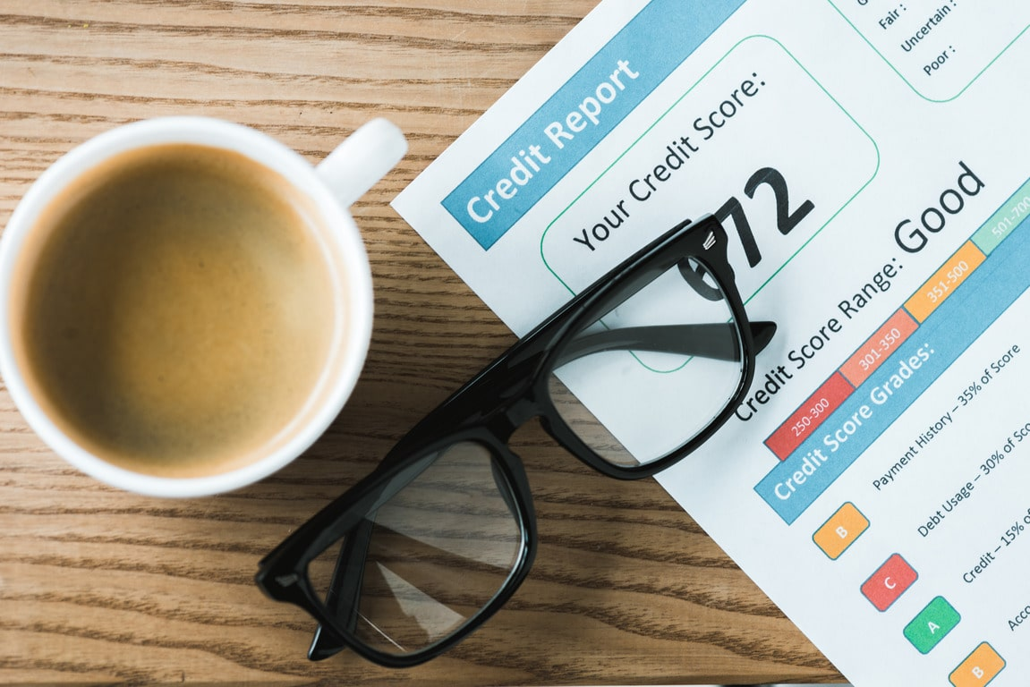 top view of cup with coffee near paper with credit report lettering on paper and glasses on table