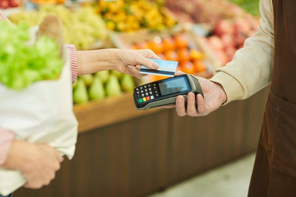 Woman buying affordable groceries with her debit card.