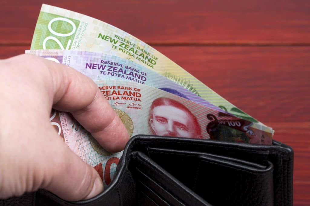 Hand reaching in wallet to pull out savings in New Zealand dollars.